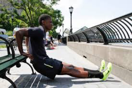 man doing tricep dips from a bench